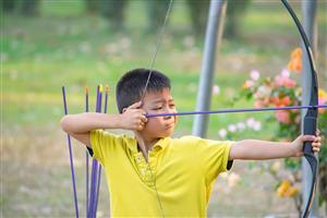 Boy practicing archery at camp